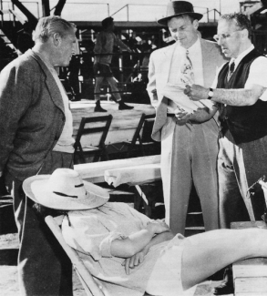 http://e-pic.tumblr.com/post/22514519446/kate-snoozes-on-the-set-of-pat-and-mike-director Hepburn naps while George Cukor talks to Spencer Tracy and Aldo Ray